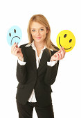 Woman holding frowny and smiley face cards