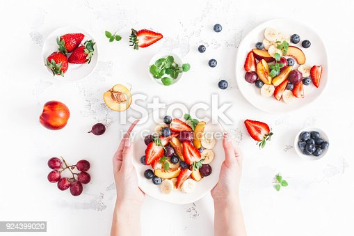 640978994 istock photo Woman holding fruit salad. Flat lay, top view 924399020