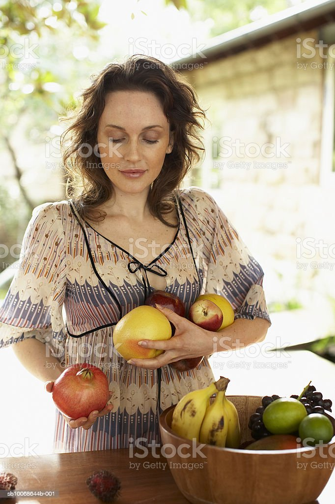 Woman holding fruits, smiling 免版稅 stock photo