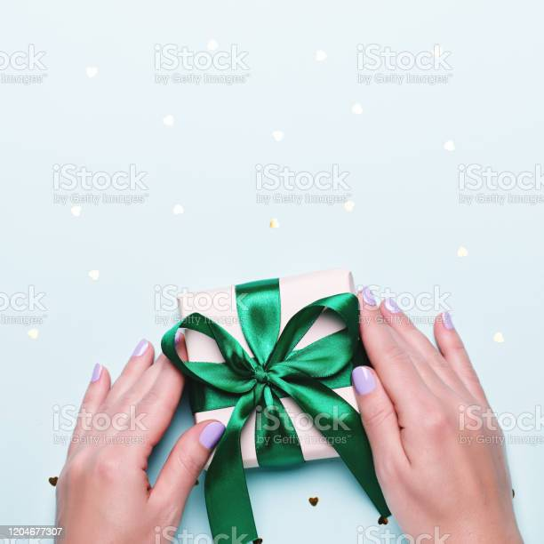 Woman holding gift box in green color on pastel blue background with picture id1204677307?b=1&k=6&m=1204677307&s=612x612&h=ng 2a47rz rsyth2zkwuznu7qlimzgrwlxx2ppcuurg=