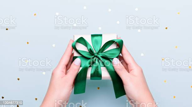 Woman holding gift box in green color on pastel blue background with picture id1204677310?b=1&k=6&m=1204677310&s=612x612&h=txsj1dbazircc3ikzamxyq7maaxopsxm1iw1akcdrxc=