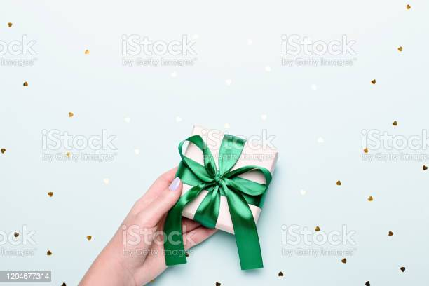 Woman holding gift box in green color on pastel blue background with picture id1204677314?b=1&k=6&m=1204677314&s=612x612&h=1 ahvuxv6wrbhifv0bc9jyhtnefhbulvs9e3q0n6nu0=