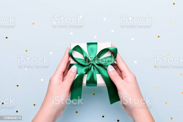 Woman holding gift box in green color on pastel blue background with picture id1206050015?b=1&k=6&m=1206050015&s=612x612&h=xgdx sczqhpouxrttp gc7xp6yqfvbzworv0dubw2u0=
