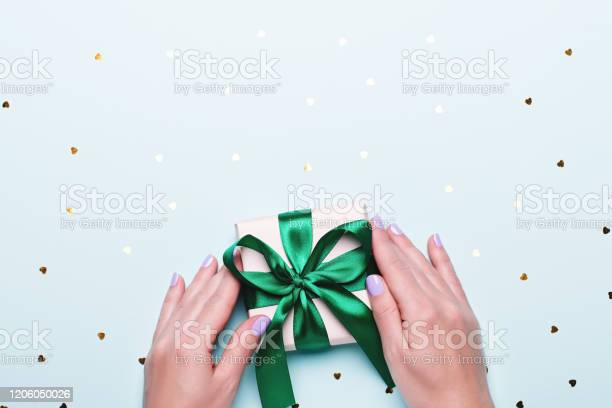 Woman holding gift box in green color on pastel blue background with picture id1206050026?b=1&k=6&m=1206050026&s=612x612&h=o8nat5ccw7 klh9u8v53veq3r2dlfzyp6zv wn9bfte=