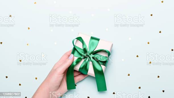 Woman holding gift box in green color on pastel blue background with picture id1208927602?b=1&k=6&m=1208927602&s=612x612&h=xzpcddo1ddbxd8u kcqmortpitw fxiyuo q5lr7t04=