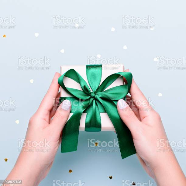 Woman holding gift box in green color on pastel blue background with picture id1208927603?b=1&k=6&m=1208927603&s=612x612&h=3wu8yoqc2gthkgfatqfzlb3dqcxcx8z8j6czeqroypo=