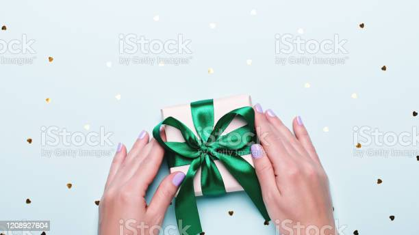 Woman holding gift box in green color on pastel blue background with picture id1208927604?b=1&k=6&m=1208927604&s=612x612&h= zvm 9k68xoy10p9fbatfewer7gjh5vozzdrmhtlgmo=