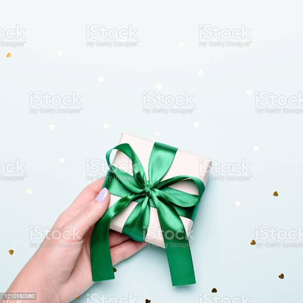 Woman holding gift box in green color on pastel blue background with picture id1210162080?b=1&k=6&m=1210162080&s=612x612&h=pnx7ql16p70ymhaxqgr6mhslcqqkhituizdtptxdddy=