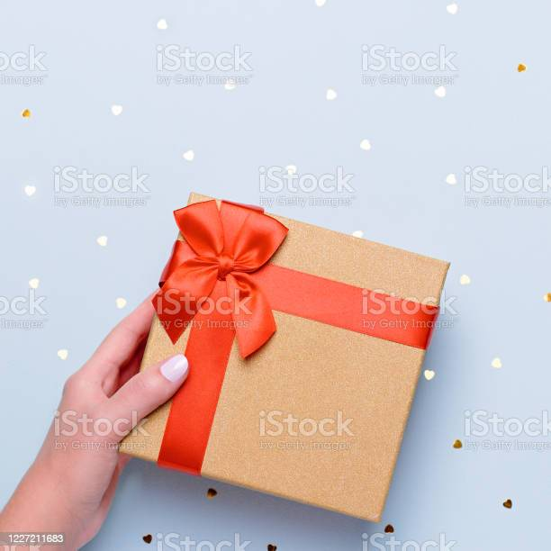 Woman holding gift box in red and gold color on pastel blue with picture id1227211683?b=1&k=6&m=1227211683&s=612x612&h= zpwgilhcfuiukpmivdzjgnplm83jkbstdvemtad yw=