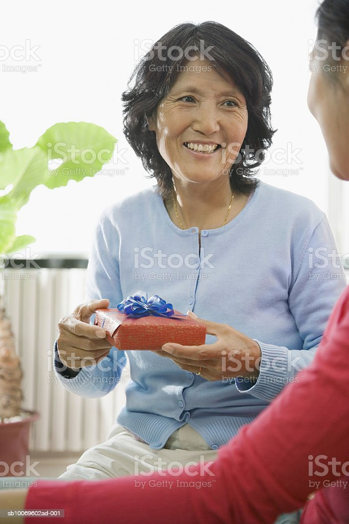 Woman holding gift box, smiling royalty-free stock photo