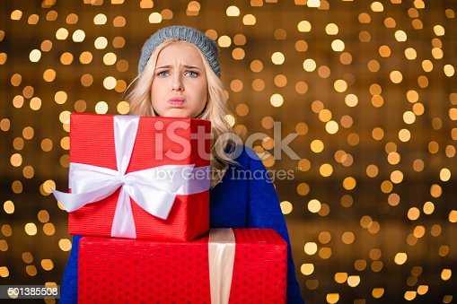 istock Woman holding gift boxes over holidays lights background 501385508