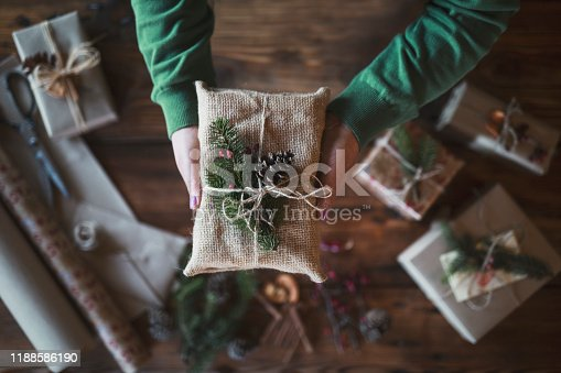 Close up stock photo with unrecognizable female hands holding gift wrapped with textile and natural decoration.