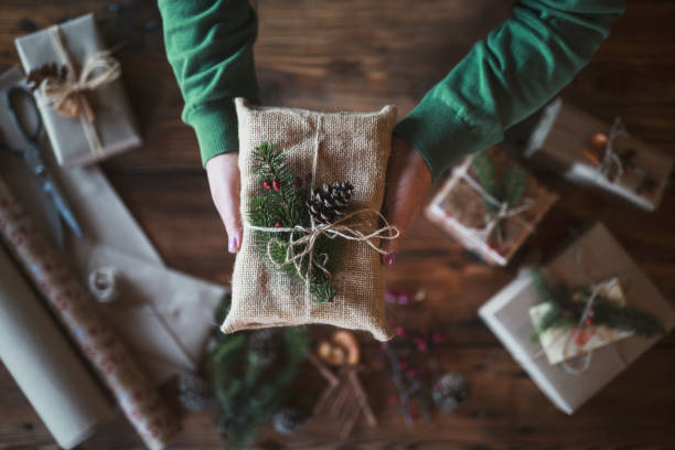 Woman Holding Gift Close up stock photo with unrecognizable female hands holding gift wrapped with textile and natural decoration. wrapping stock pictures, royalty-free photos & images