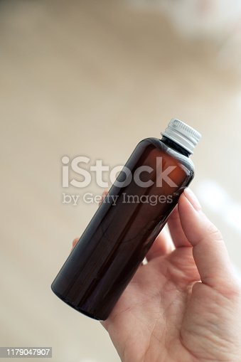 1167558793 istock photo Woman holding glass cosmetic  brown bottle 1179047907