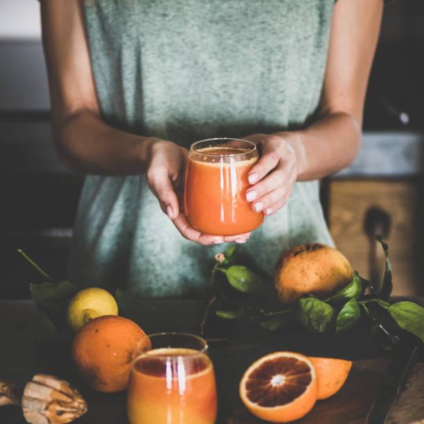 kobieta trzymająca szklankę świeżego soku pomarańczowego z krwi, kwadratowa uprawa - detoks zdjęcia i obrazy z banku zdjęć