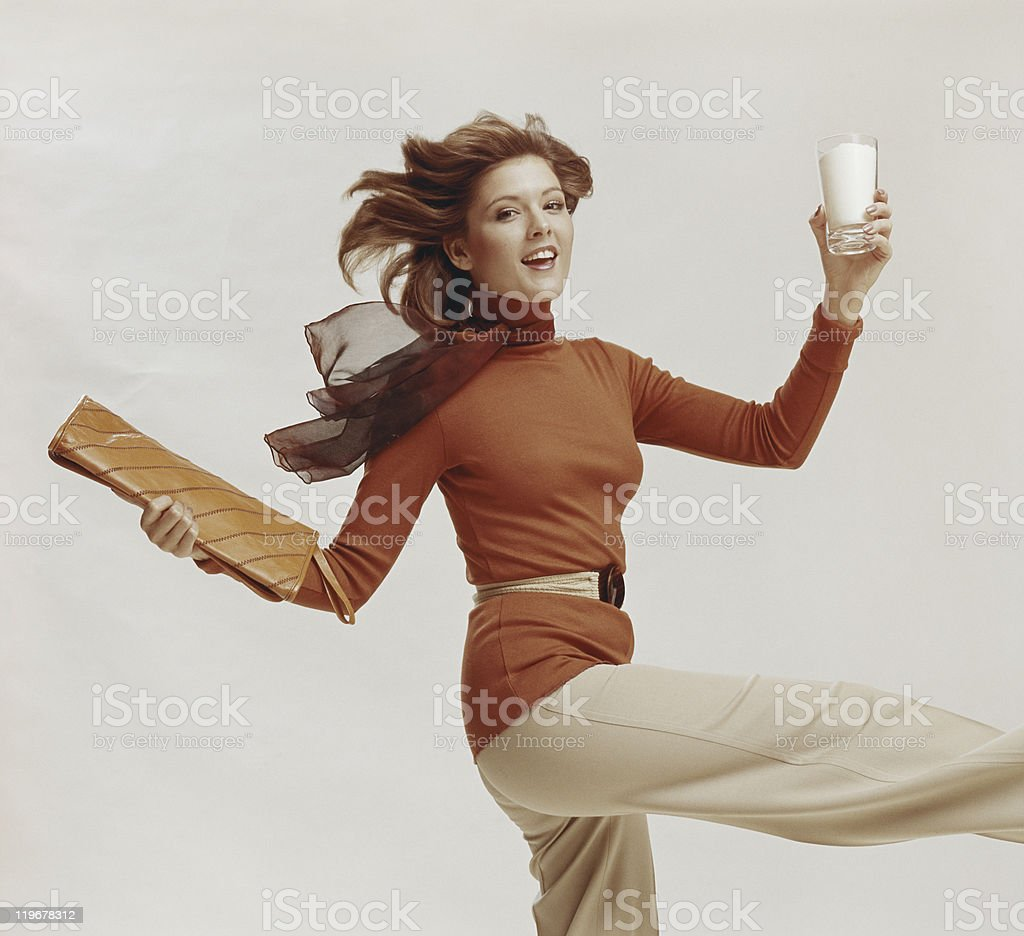 Woman holding glass of milk and file, smiling, portrait stock photo