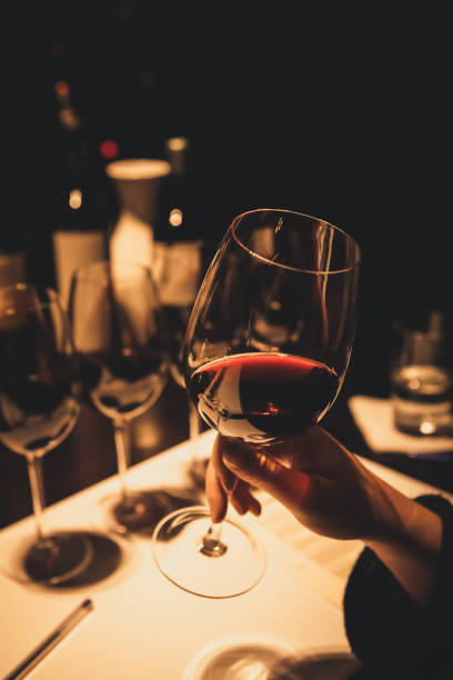 Woman holding glass of red wine during a wine tasting event. stock photo