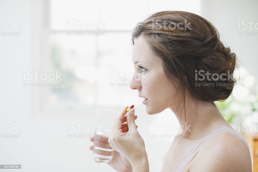 Woman holding glass of water and taking capsule stock photo