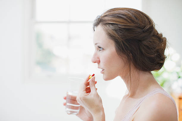 Woman holding glass of water and taking capsule  woman taking pills stock pictures, royalty-free photos & images