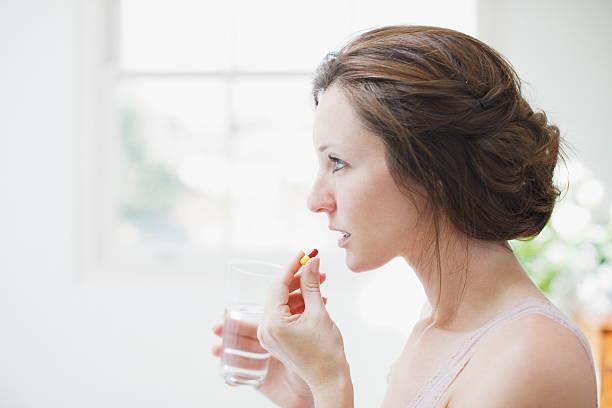 Mujer agarrando vaso de agua y tomar la cápsula - foto de stock