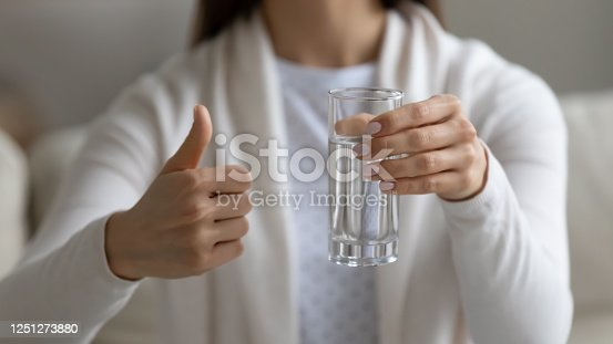 Close up image woman sit on couch holding glass of clean water showing thumbs finger up gesture, intake of enough quantity of aqua every day, improve metabolism, remove toxins, health benefits concept