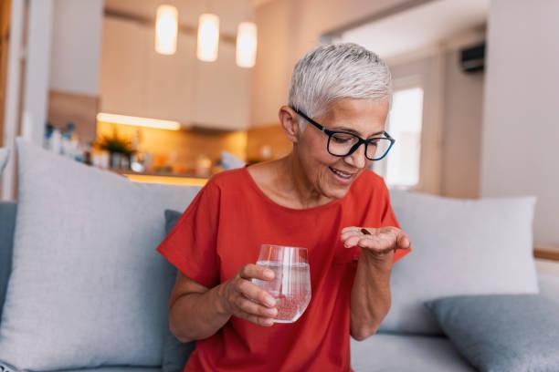 Frau hält Glas Wasser, die Pille – Foto