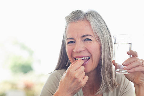 woman holding glass of water taking pill - vitamin stock pictures, royalty-free photos & images