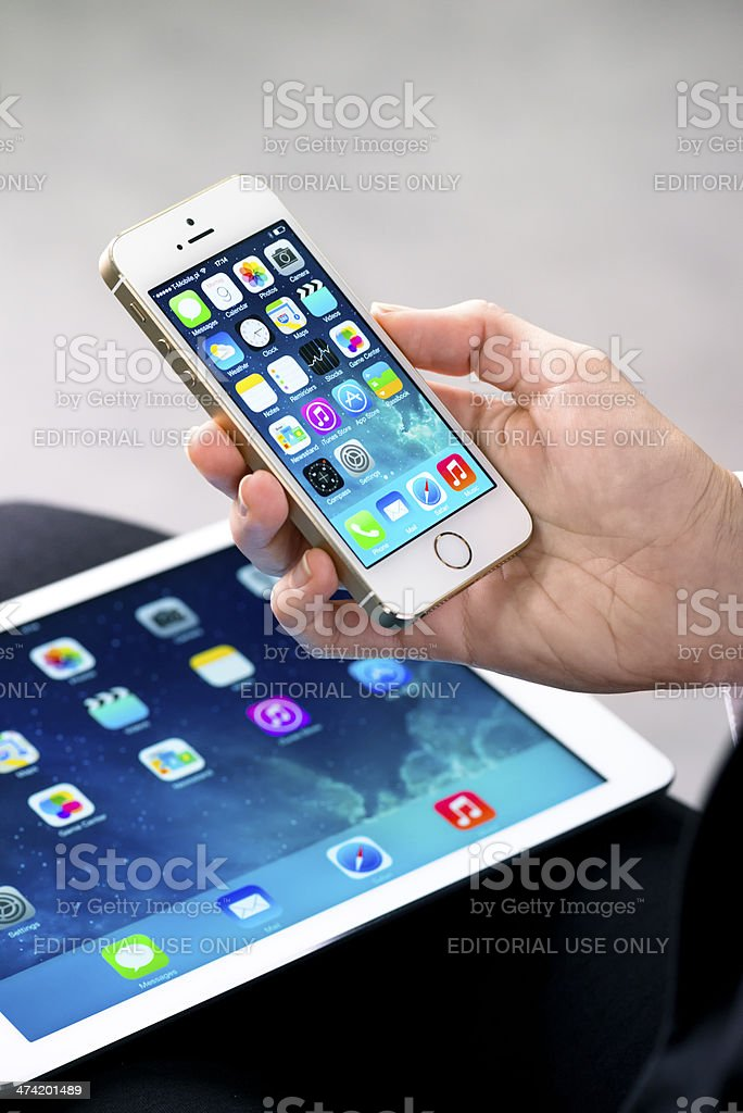 Woman holding gold iPhone 5S and iPad Air stock photo