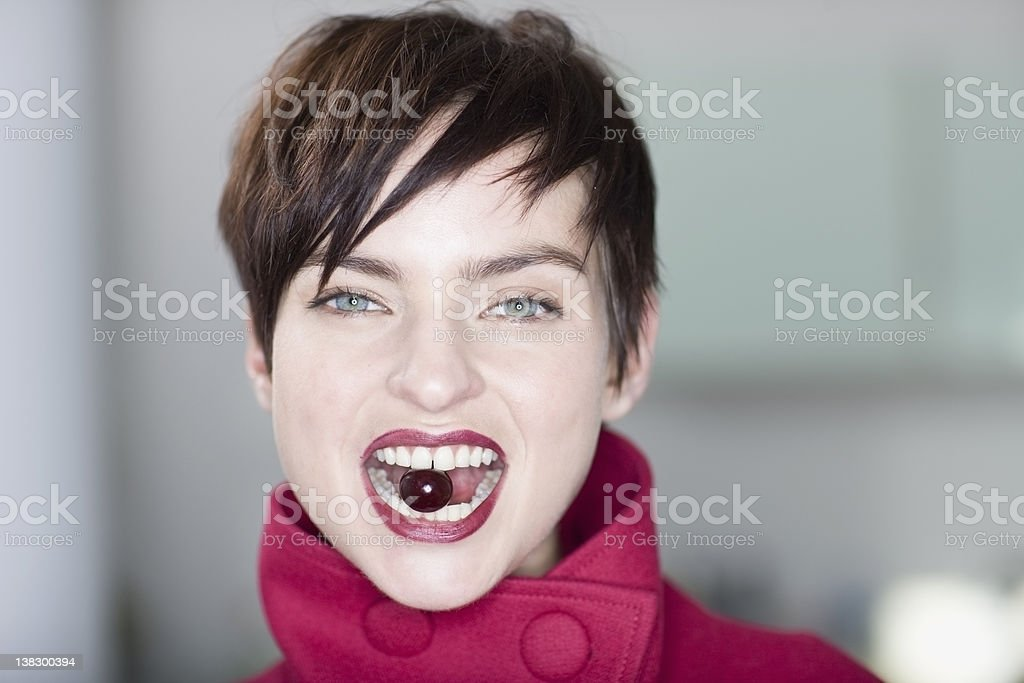 Woman holding grape between her teeth stock photo