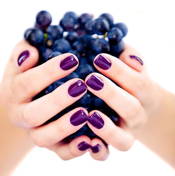 frau holding trauben - herbst nagellack stock-fotos und bilder