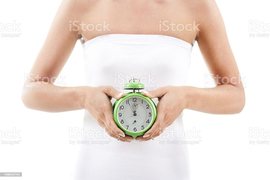 Woman holding green clock in hands depict biological clock stock photo