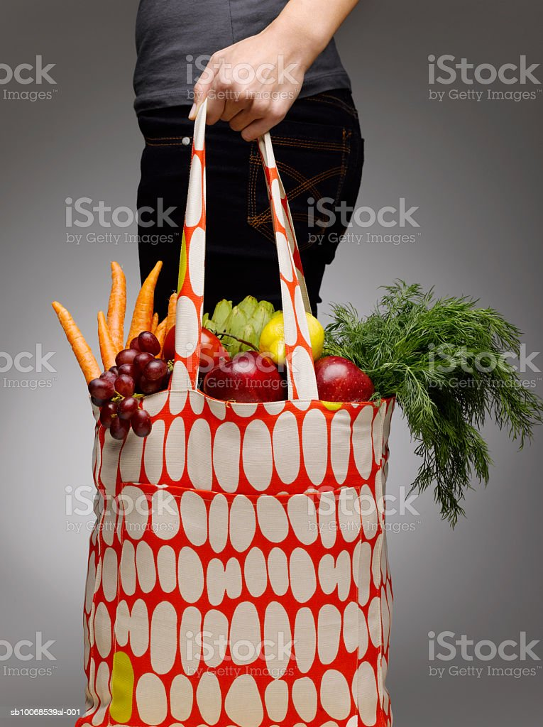 Woman holding grocery bags containing vegetables, mid section royalty-free stock photo