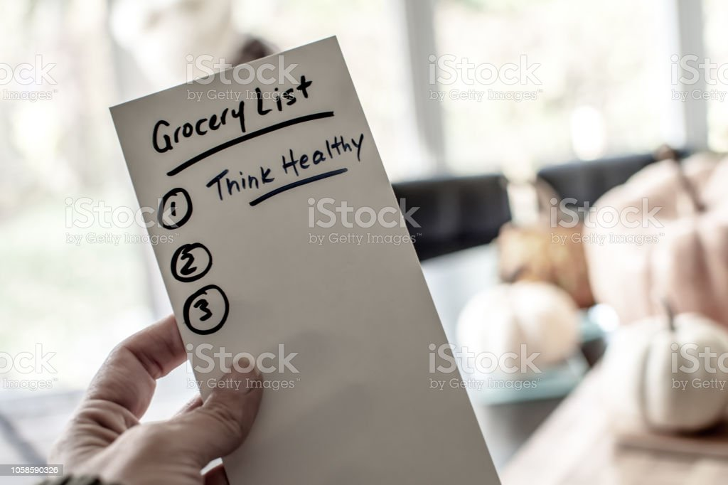Woman holding grocery list healthy eating  and lifestyle for the holidays in home kitchen with words think healthy stock photo