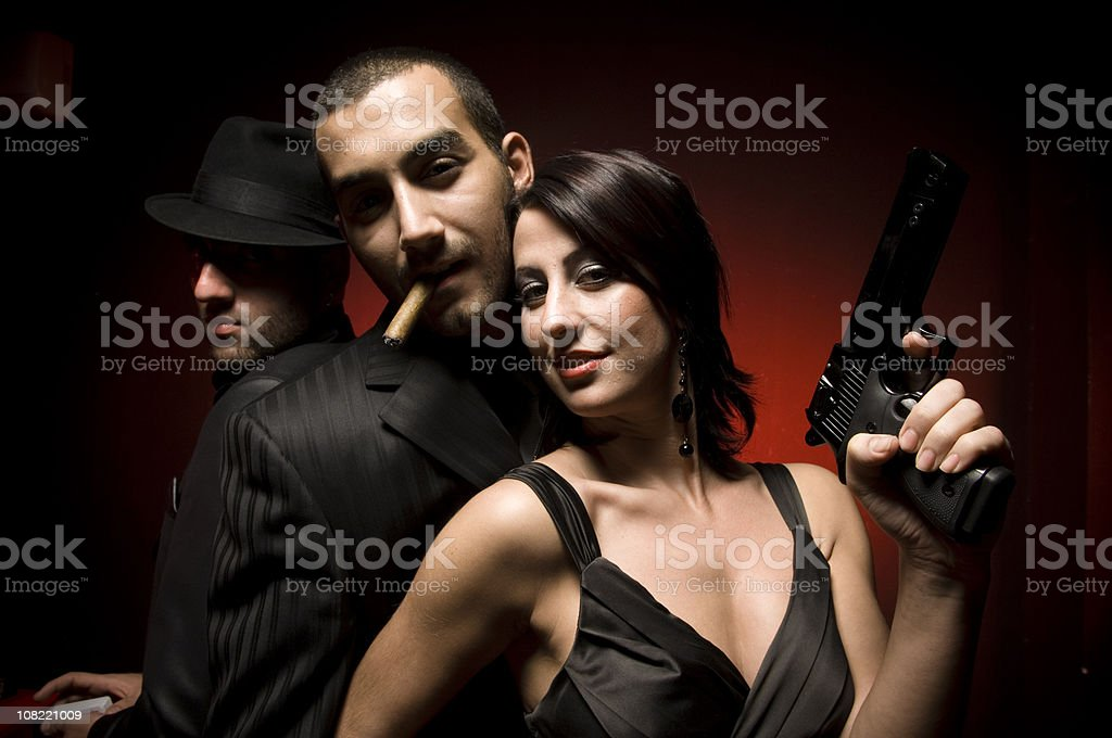 Woman Holding Gun Posing with Two Men in Suits stock photo