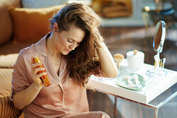 woman holding hair oil at modern home in sunny winter day stock photo
