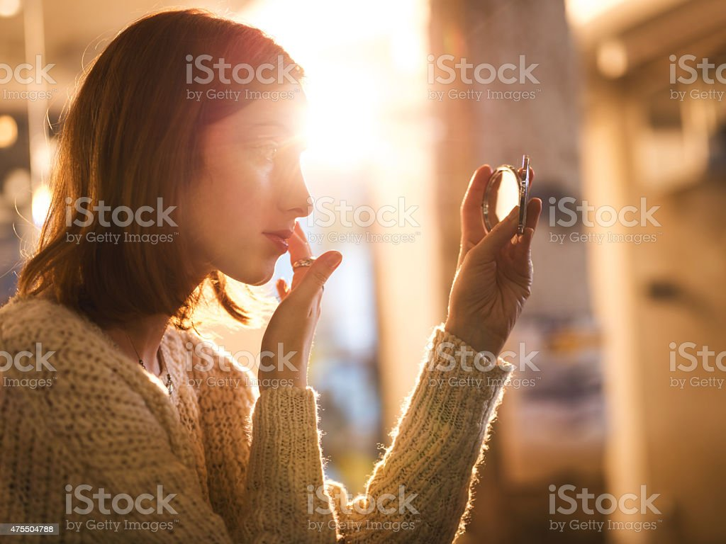 Woman holding hand mirror and fixing make-up. stock photo