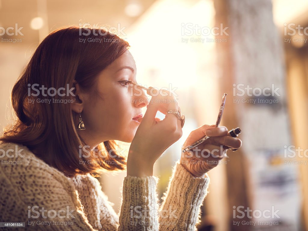 woman holding hand mirror. Woman Holding Hand Mirror And Fixing Make-up. Royalty-free Stock Photo