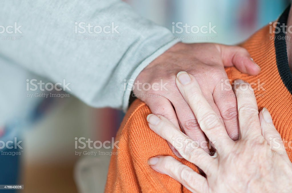 Woman holding hand on the shoulder of a Senior woman stock photo