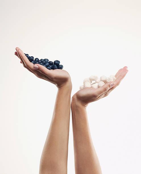 frau holding handvoll blaubeeren über handvoll zucker würfel - grape sugar stock-fotos und bilder
