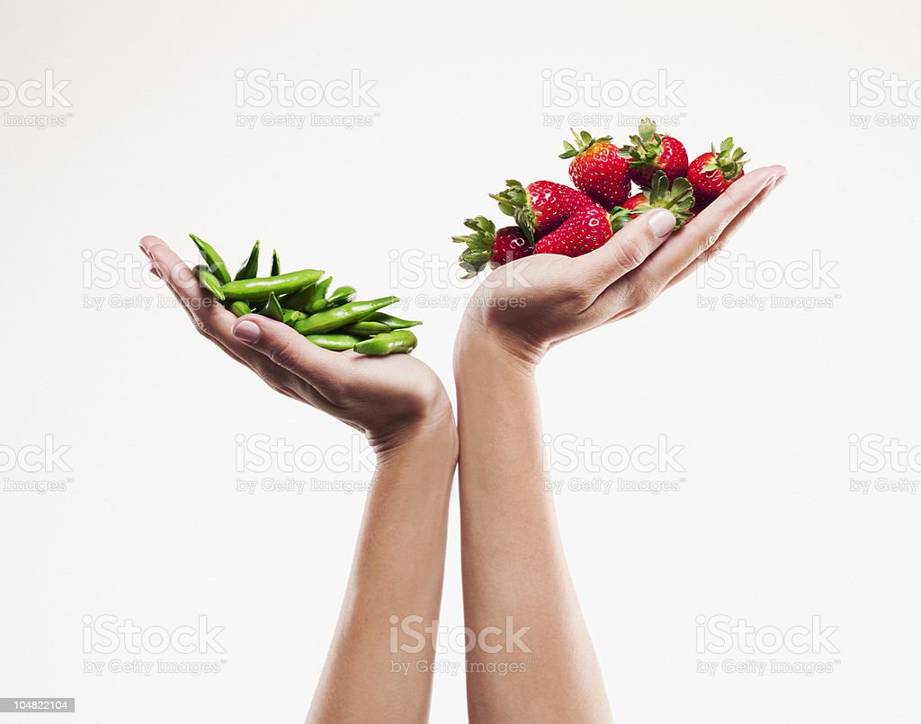Woman holding handful of strawberries over handful of pea pods stock photo