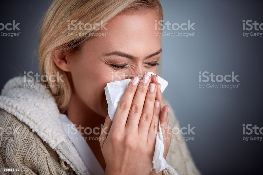 Woman holding handkerchieif blowing nose stock photo
