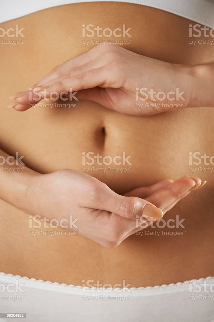 Woman Holding Hands In Front Of Stomach stock photo