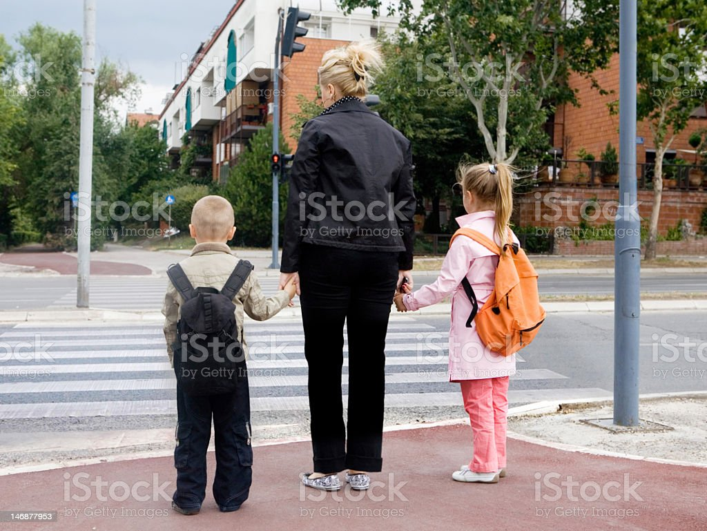 Woman holding hands of two kids representing traffic safety stock photo