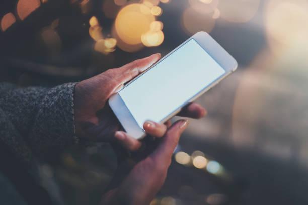 Frau mit Händen Smartphone in stimmungsvolle Stadt Nacht. Weibliche Hände mit Handy. Nahaufnahme auf unscharfen Hintergrund. Fackeln, Bokeh Effekte. – Foto