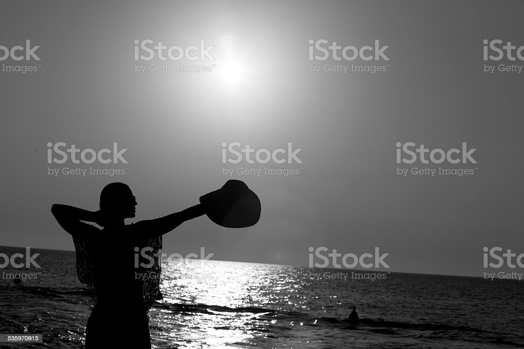 Woman holding hat at the beach, black and white photo