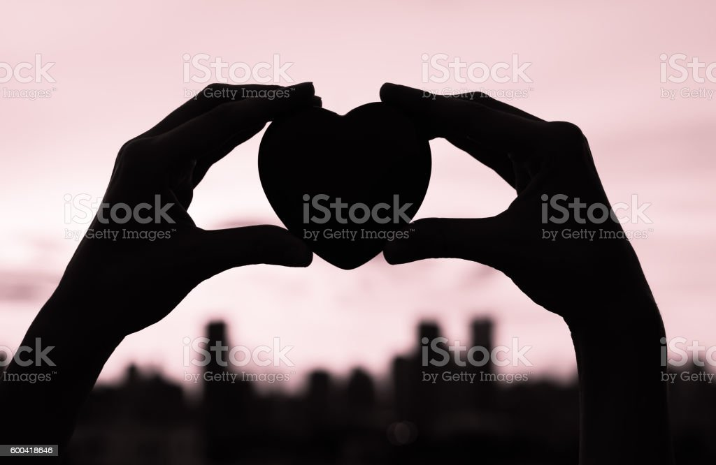 Woman holding heart in the city stock photo