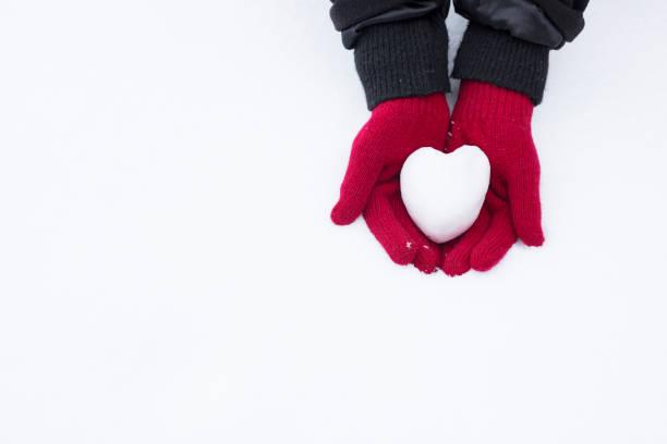 frau mit herzförmigen schneeball, close-up der hände - es schneit text stock-fotos und bilder