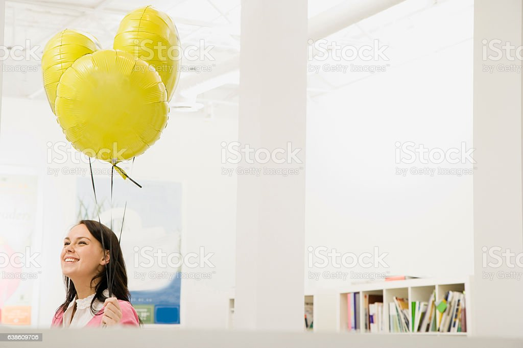 Woman holding helium balloons in office stock photo
