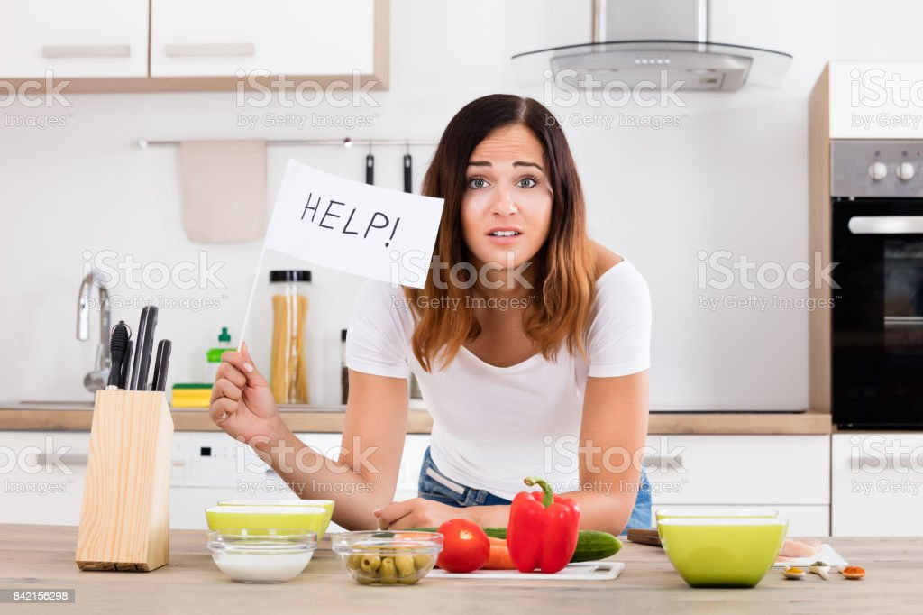 Woman Holding Help Flag In Kitchen stock photo