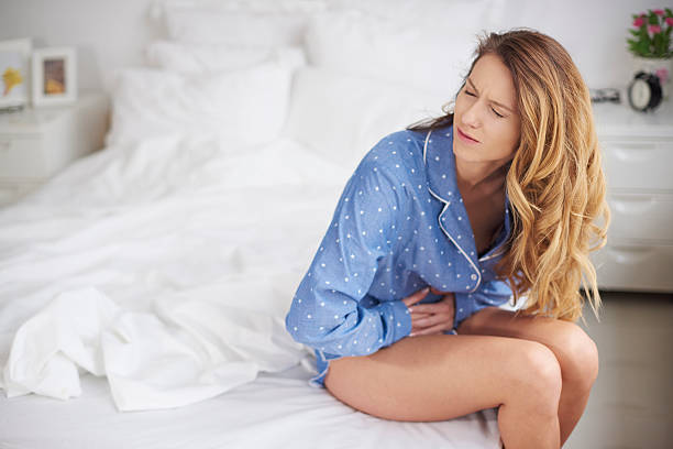 Woman holding her belly in bed stock photo